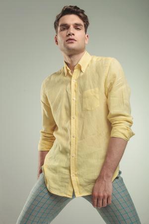 yellow shirt: Arrogant young handsome man posing on grey studio background.