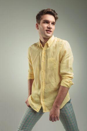 jambes �cart�es: Vue de c�t� d'un jeune homme souriant de la mode posant avec ses jambes �cart�es.
