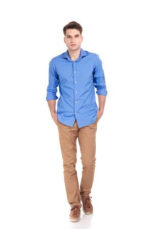 Casual jonge man die met zijn handen in de zakken op geïsoleerde achtergrond.