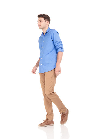 from side: Side view of a young fashion man walking on isolated background.