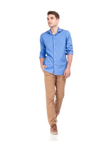 caminando: Hermoso casual hombre joven que camina con la mano en el bolsillo en el fondo aislado, mirando lejos de la cámara. Foto de archivo