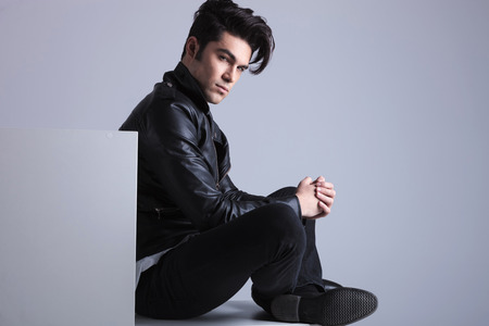 leather coat: Side view picture of a fashion man sitting on the floor, looking at the camera while holding his hands together.