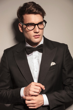 man in tuxedo: Portrait of a handsome business man looking away while fixing his sleeve.