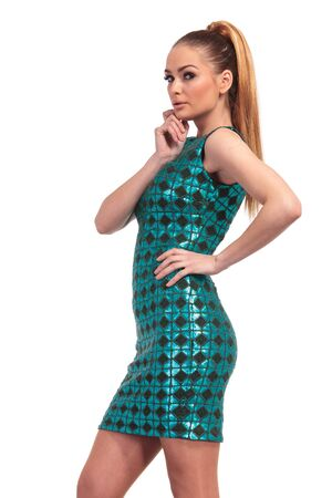 Side view of a sexy young fashion woman in a slim blue dress, looking at the camera. Stock Photo - 40253428