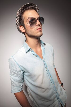 casual fashion: Side view of a young casual fashion man wearing sunglasses and a hat. Stock Photo