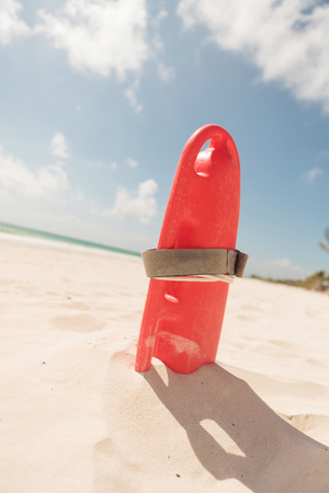 life guard: Picture of a red plastic life guard tube, on the beach.