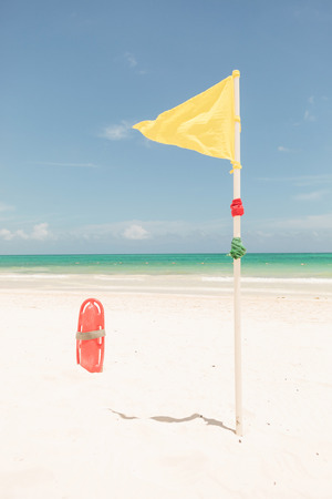 plactic: Yellow flag and red plactic lifeguard tube on th ebeach.