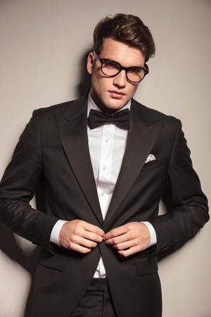 cerrando negocio: Joven elegante hombre de negocios de cerrar su chaqueta mientras mira a la cámara.