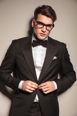 Young elegant business man closing his jacket while looking at the camera. photo