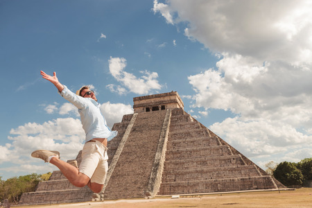 Happy young man jumping of happiness near a pyramid in Tulum, Mexico. Stock Photo