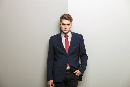 Casual young business man holding one hand in his pocket while leaning on a grey wall. photo