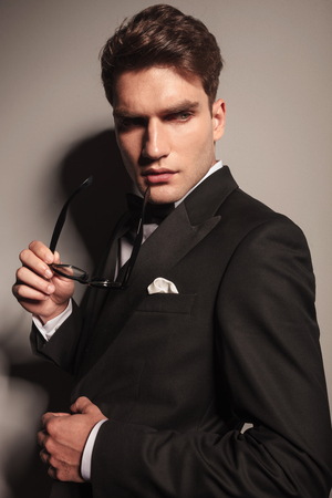 Side view portrait of a elegant young business man holding a pair of glasses in his hand. photo