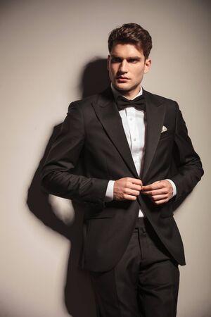 cerrando negocio: Joven apuesto hombre de negocios cerrando su chaqueta mientras se apoyaba en la pared.