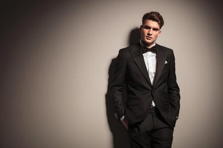 Elegante jonge zakenman leunend op een grijze muur met zijn handen in de zakken.
