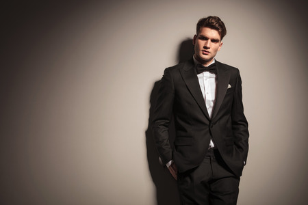 modelos hombres: Elegante joven hombre de negocios apoyado en una pared gris con las manos en los bolsillos.