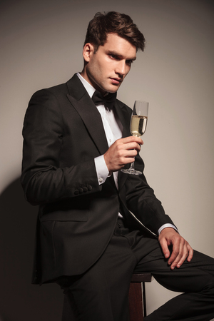 Side view of a young elegant business man sitting on a chair holding a glass of champagne.