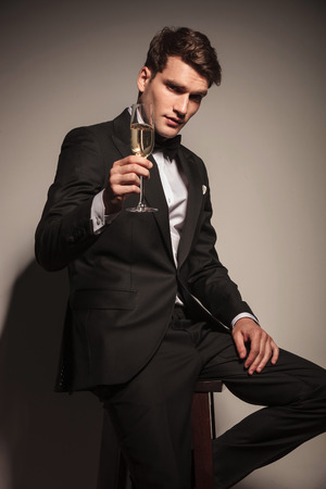 champagne: Handsome elegant business man offering you a glass of champagne while sitting on a chair.