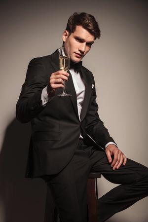 Knappe elegante business man biedt u een glas champagne, terwijl zittend op een stoel.