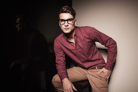 Handsome young casual man sitting on a stool resting his right hand on his leg. photo