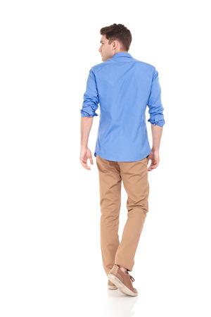 Terug oog van een jonge mode man lopen op geïsoleerde achtergrond op zoek naar zijn zijde.