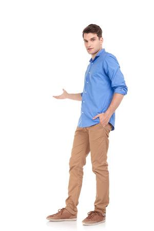 alzando la mano: Imagen de cuerpo entero de un hombre joven casul presentar algo con su mano derecha.