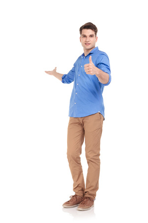 gesture: Full body picture of a young fashion man welcoming you while showing the thumbs up gesture.