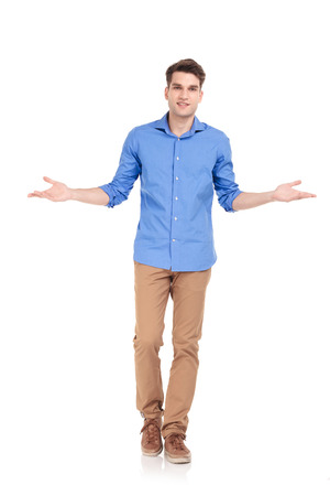 Full body picture of a young casual man walking while welcoming you.