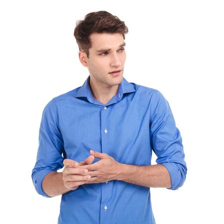 beau jeune homme: Inquiet jeune homme tenant ses mains tout en regardant à ses côtés. Banque d'images