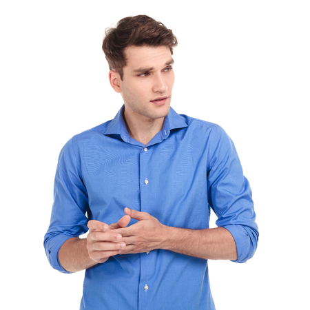 man think: Worried young man holding his hands together while looking to his side. Stock Photo
