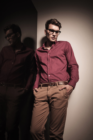 man looking down: Young business man looking down while leaning on a wall with his hands in pockets.