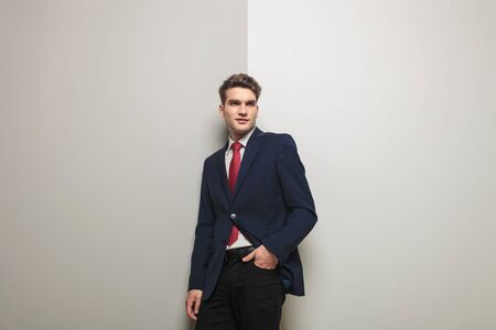 lean on hands: Young business man holding one hand in his pocket while leaning on a grey wall.