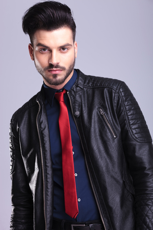 Portrait of a young casual business man wearing a leather jacket on grey studio background. photo