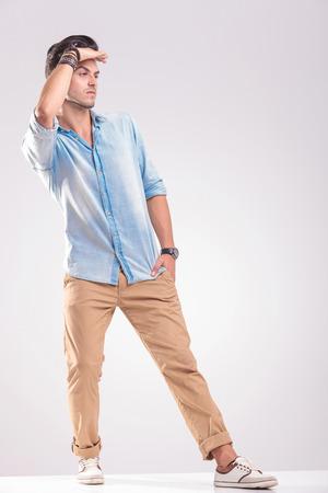 lejos: Vista lateral de un hombre joven ocasional celebración de su mano a la frente que parece lejana.