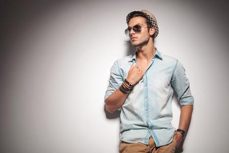 Attraktives Art und Weisemann Wegschauen, während zieht sein Hemd.