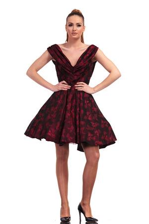 tacones rojos: Preciosa mujer elegante de moda de pie con su handsaround su cintura.