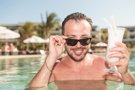 Hot sexy man enjoying a cold cocktail while stamding in the pool.