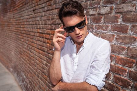 lean on hands: Young fashion man leaning on a brick wall while looking down and touching his sunglasses.