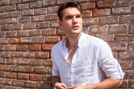 from side: Portrait of a handsome young fashion man leaning on a brick wall while looking away from the camera.