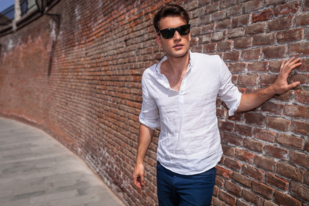 casual fashion: Handsome casual fashion man posing while holding his hand on a brick wall. Stock Photo