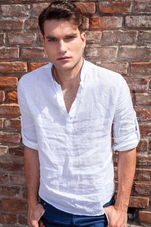 modelos hombres: Retrato de un hombre de moda joven, apoyado en una pared de ladrillo, mientras que la celebración de los pulgares en los bolsillos.