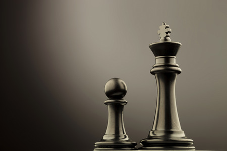 battle plan: black king chess piece near the black pawn Stock Photo