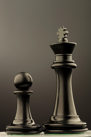 battle plan: black king and pawn of chess , studio picture Stock Photo