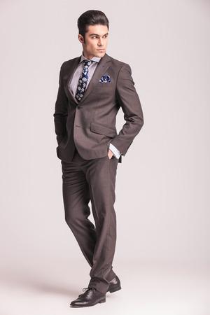 Zijaanzicht beeld van een jonge zakenman met zijn handen in de zakken, terwijl terug te kijken.