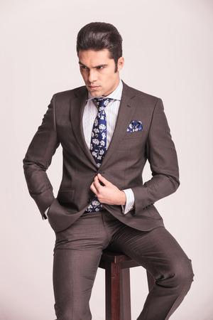 cerrando negocio: Atractivo joven hombre de negocios de cerrar su chaqueta mientras se está sentado en un taburete. Foto de archivo