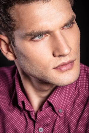 man face close up: Close up of a young handsome man looking away from the camera, thinking. Stock Photo