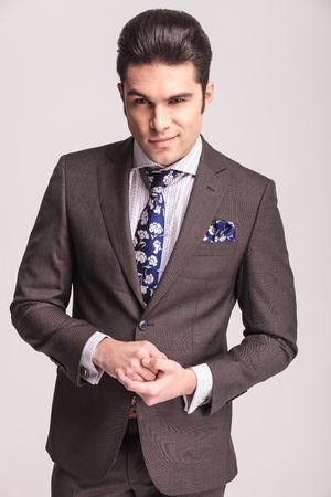 manos juntas: Sonriente hombre de negocios joven que presenta en el estudio de fondo gris, con las manos juntas.