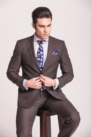 cerrando negocio: Apuesto hombre de negocios mirando hacia abajo, mientras que el cierre de su traje. �l est� sentado en una silla marr�n.
