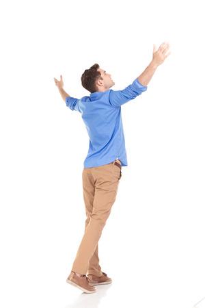 Terug oog van een jonge mode-man met zijn handen omhoog, het vieren. Stockfoto