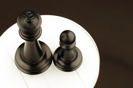 battle plan: black pieces of chess, king near pawn on white circle
