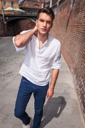 modelos hombres: Handsome casual man walking near a brick wall holding his hand to the neck.